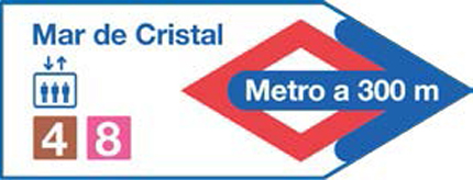 A sign in the shape of an arrow that tells you that the nearest Metro station is 300 metres away and has a lift.