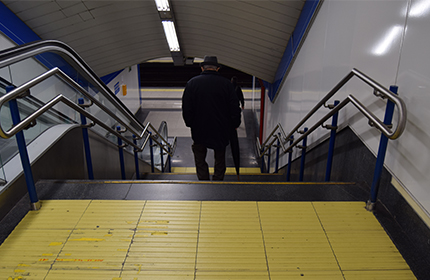 A person walking down the stairs of a station