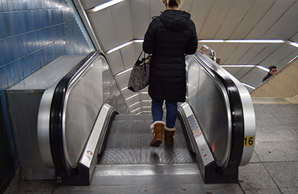 A person at the top of an escalator