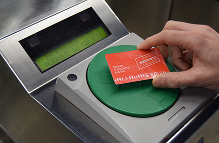 A hand touching the card on the green circle of the turnstile