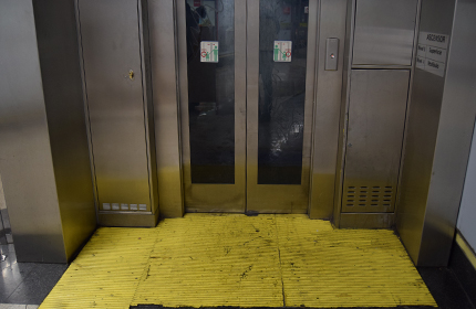 Yellow signs at the entrance of the lifts