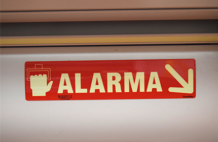 Red sign indicating the location of the alarm handle