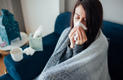 A woman with a blanket over her shoulders blowing her nose