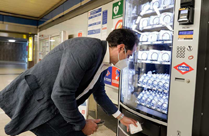 Someone purchasing alcohol-based sanitiser from a vending machine